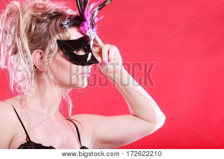 Party entertainment time concept. Woman with carnival mask. Lady wearing elegant blak dress she has blonde hair.