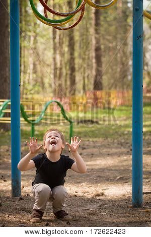 Portrait of cute kid boy jumping on the climbing frame. Young boy climbing on playground during summer. Child enjoys climbing in a children's playground outdoors.