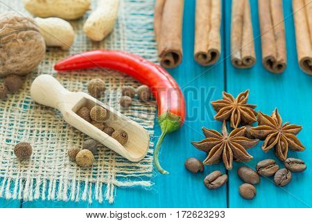 red chili pepper coffee beans cinnamon sticks and star anise on wooden table.