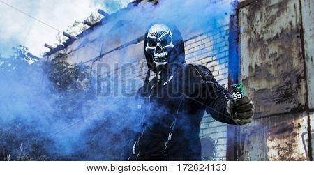 Male holding blue smoke stick grenade up in the air