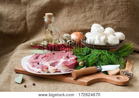 Uncooked meat : raw fresh beef pork ready to cooking with garlic onions parsley dillmushroomsquail eggsseasonings salt coriander and red hot pepper on wood table. Raw meat with condiments.