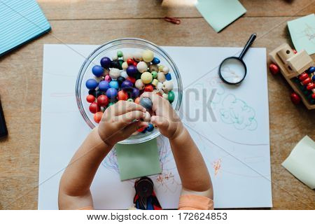 High angle view of a toddler holding beads over a bowl