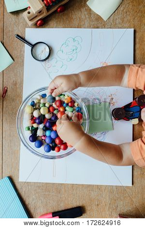 High angle view of a toddler choosing beads from a bowl