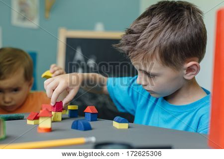 Two brothers playing with wooden blocks and building little houses