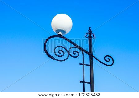 Street lamps round white cap black pole is located on the sky background.