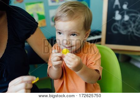 Happy toddler learning shapes and colors with his mother