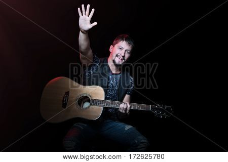 Bearded guitarist playing the guitar and picked up an open hand isolated on black background