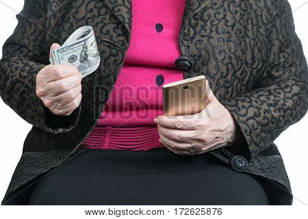 Old woman holds in one hand a pack of dollars in the other a golden mobile phone, close-up