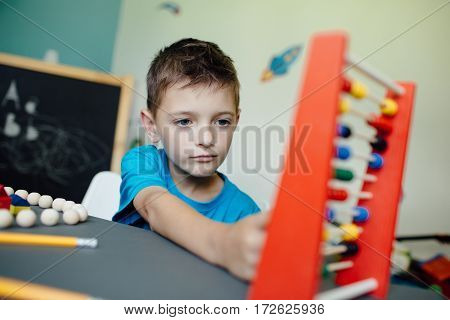Schoolboy learning maths with an abacus at home