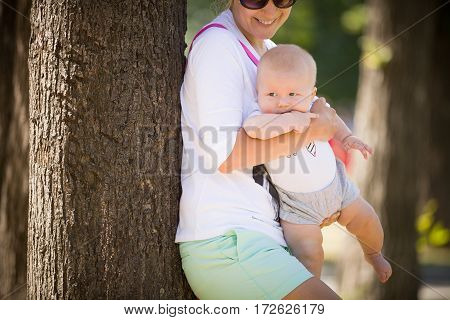 Happy young woman with her little infant baby having fun in the park. Mother with a child walking on sunny day. Mom and son outdoors. Woman holding adorable baby in her hands.