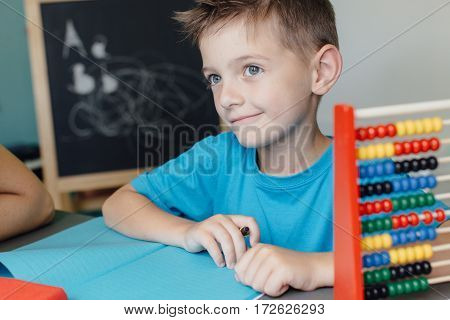 Smiling schoolboy working on math homework with an abacus
