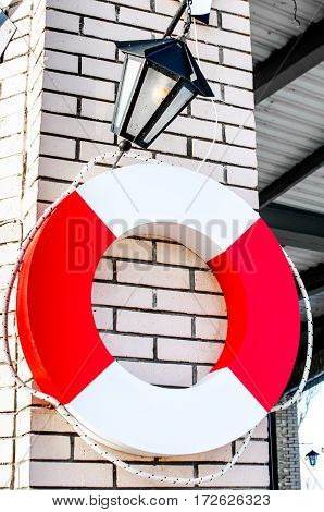 Lifebuoy as a security symbol of white and red color on a mooring on a brick wall