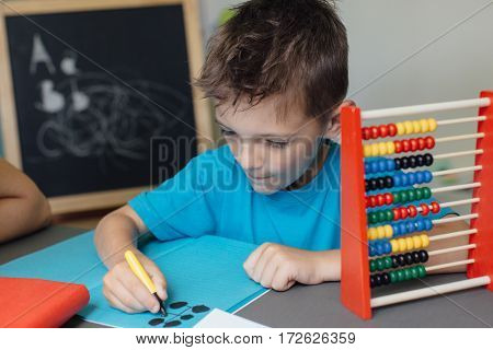 Focused schoolboy working on math homework at home