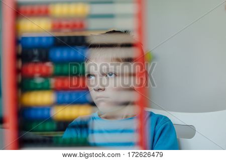 Absent minded schoolboy gazing away through an abacus