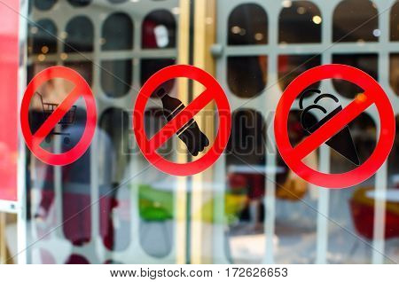 sign ban entry to the shop with ice cream food cart soda water. crossed-out icon on the window glass