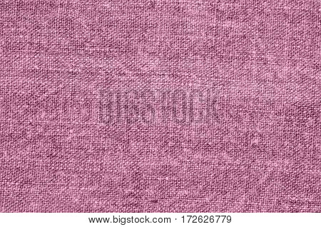 Homespun hemp cloth. Close-up of texture fabric cloth textile background. Homespun hemp fabric material. Homespun hemp canvas. Natural authentic cloth. Dusty pink color