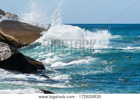 A wave exploding on a rocky shore in white spray