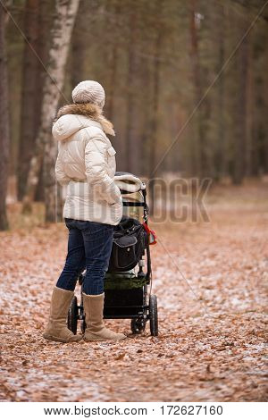 Young woman walking with a stroller in the forest. Mother with a child. Girl with carraige ourdoors. Lifestyle concept