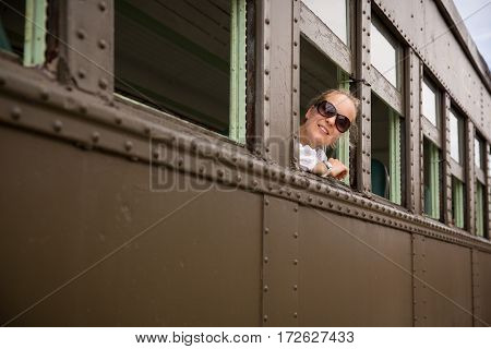 Happy woman in sun glasses sitting in the old train and looking out the window. view from outside. Girl in retro train. Vacation trip.