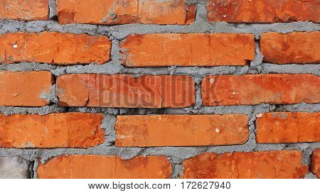 red brick wall with the grey cement between blocks