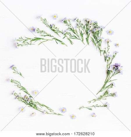 Flowers wreath. Frame with purple daisy flowers on white background. Flat lay top view