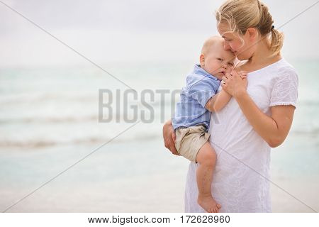 Portrait of young mother with her adorable little boy on the ocean beach. Happy woman hugging a baby and enjoying vacation by the sea. On the empty beach. Motherhood family and lifestyle concept