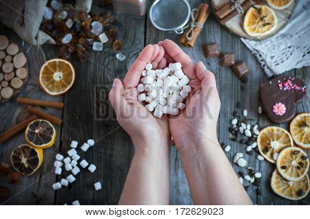 Two female hands holding a bunch of white marshmallow on the table top view
