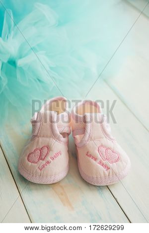 Pink booties for newborn baby on a wooden turquoise background