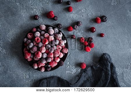 Frozen raspberry blueberry cranberry on dark background. Frozen fruit. Top view flat lay