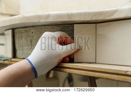 Worker's hand puts the piece of tile on the curved wall under a sink.