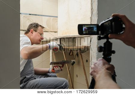 Worker installs ceramic tiles. The operator is shooting this process using camcorder and tripod.