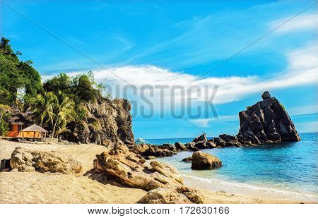 Tropical beach with stones and rocks. Sand beach view with cloudy sky. Nature of tropical island. Exotic seaside digital illustration. Still sea water and sunny beach. Relaxing escape image