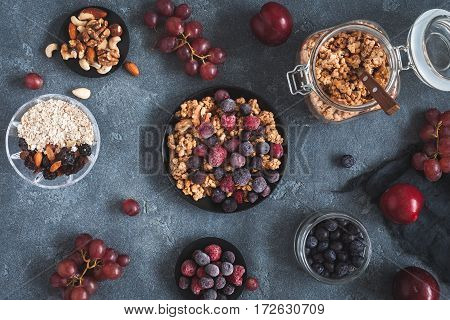 Breakfast with muesli fruits frozen berries nuts on dark background. Healthy food concept. Flat lay top view