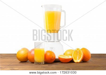 Close up view on a table with fruits for making a detox smoothie from oranges and grapefruit with a blender and juice on wooden table on white background. Mixed exotic fruit.
