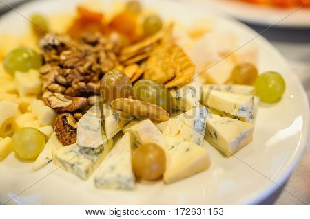 Cheese Plate Composition With Nuts And Grapes
