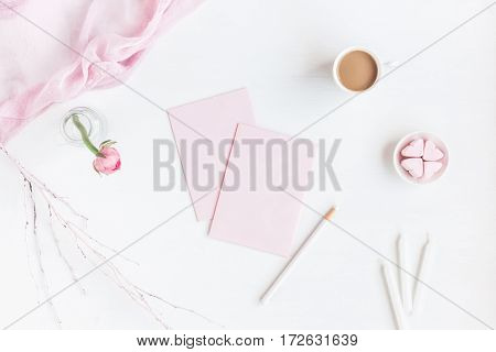 Feminine workspace with notebook cup of coffee paper blank pink flower pencil. Business concept. Flat lay top view