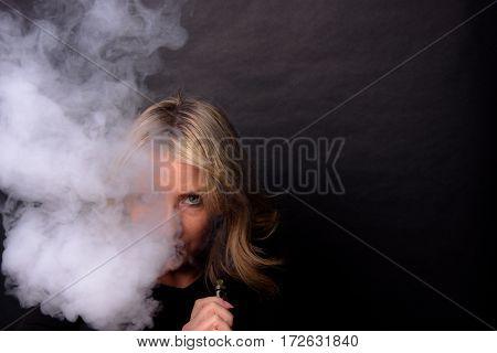 Low Key Image of A Woman making a large Vapor Cloud