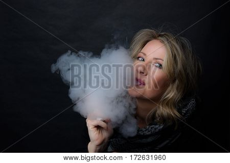 Low Key Image of A Woman blowing Vapor