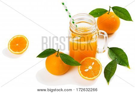 Orange slices and juice in a mason jar mug with straw isolated on white background.