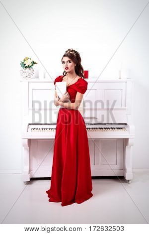 Elegant Woman In A Long Red Dress Holds Unrecognized Notes, Standing At The Piano In A White Room
