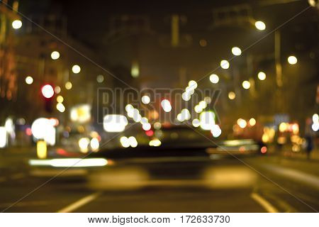 Night city view in blur. City street blurry photo. Streetlife bokeh image. Street view with pedestrians and cars defocused image. Road in big city bokeh image. Night city lifestyle blurry background