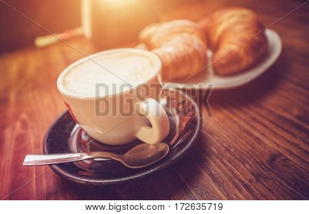 Cappuccino Coffee Time. Freshly Made Cappuccino and Tasteful Croissants on the Wooden Table Somewhere in the Italy.
