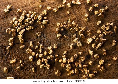 Gold nuggets scattered on a old wooden mining table.  Intentionally shot with extremely Shallow depth of field. Soft focus.