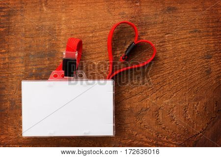 Blank security card or ID card with red neck strap forming a shape of a heart, on rustic wooden background. For adding your message or corporate information of your choice.