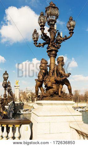 Baroque bronze lantern with Cupids on the bridge of Alexander III in Paris France