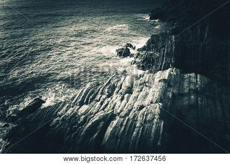 Rocky Mediterranean Sea Shore in the Italian Liguria Region near La Spezia. Mediterranean Landscape and Geology. Dark Bluish Color Grading.