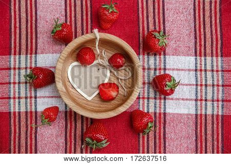 Red Fresh Strawberries in the Wooden Plate with Heart Wish Card on the Check Tablecloth.Breakfast Organic Healthy Tasty Food.Wish Card.Cooking Vitamins Ingredients.Summer Fruits.Top View