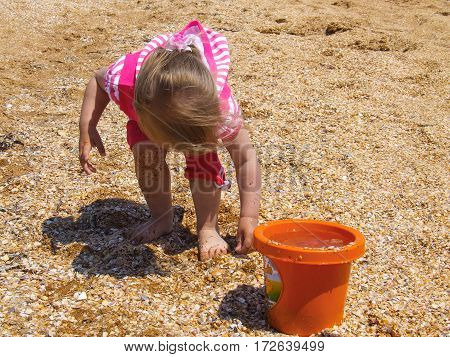 The child pours sand into the bucket