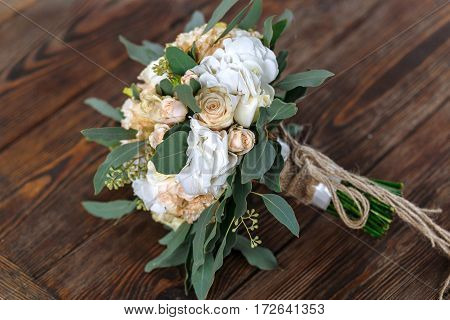 Bouquet of white flowers cream flowers and greens lying on a wooden surface. Wedding bouquet