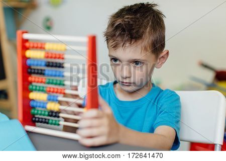 Focused schoolboy learning maths with an abacus